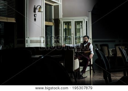 Man sitting at table served with bottle of wine and glasses in restaurant. Brutal hipster with beard in brown vest and trousers. Alcohol and appetizer. Unhealthy lifestyle and bad habits