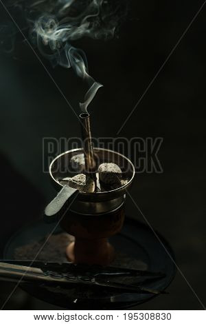 Hookah charcoal in metallic cup with smoke and tweezers or forceps tool on black background. Smoking and addiction. Drug and relax.