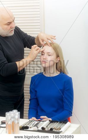 Man applying foundation cream on girl face skin. Woman or pretty fashionable model with long blond hair in blue dress sitting at table with cosmetic kit in beauty salon. Visage makeup and skincare