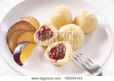 Close up of austrian popular dish called knoedel with plum jam and cinnamon on white plate