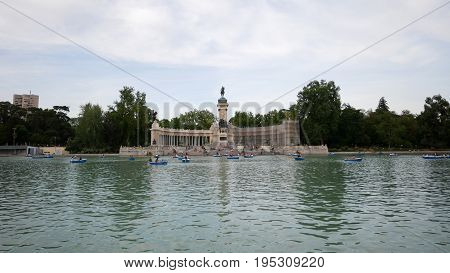 Landscape of tourists and local people on boats at pond of Retiro park with background of Monument Alfonso XII. Half of the monument is renovating.