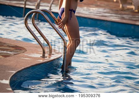 A girl in a swimsuit descends into the pool .