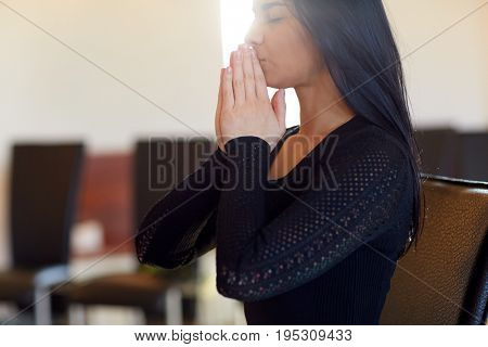 people and mourning concept - close up of unhappy woman praying god at funeral in church