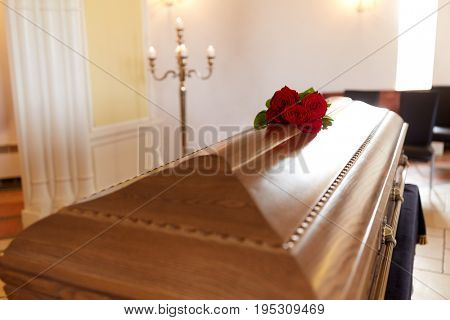 funeral and mourning concept - red rose flowers on wooden coffin in church