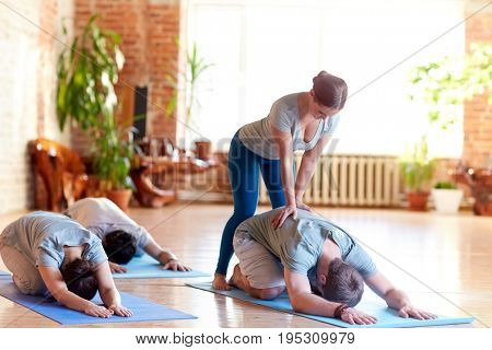 fitness, sport and healthy lifestyle concept - group of people with personal trainer doing yoga hare pose on mats in gym or studio