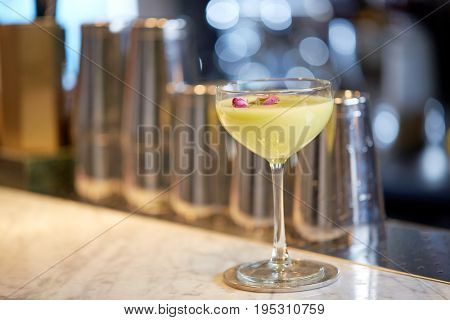 alcohol drinks and luxury concept - glass of cocktail at bar