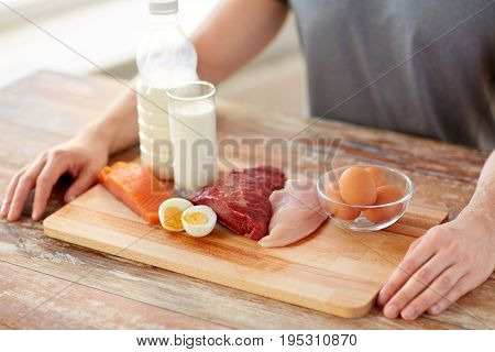 sports nutrition, healthy eating and people concept - close up of male hands with food rich in protein on wooden cutting board
