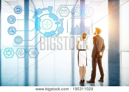 Back view of young businessman and woman looking at digital business hologram in bright office interior with sunlight. Technology future innovation and communication concept. 3D Rendering