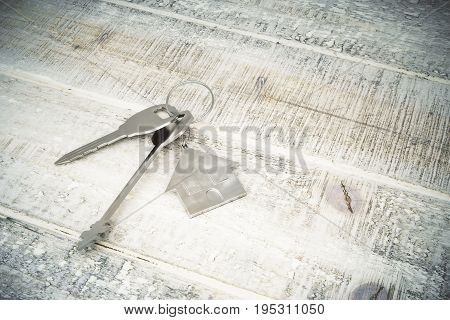 Top view of metal keys with house keychain placed on aged wooden background. Mortgage concept. 3D Rendering