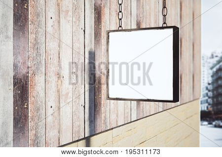 Blank square stopper handing on wooden building in bright city. Advertising concept. Mock up 3D Rendering