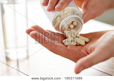 healthcare, medicine, nutritional supplements and people concept - close up of man pouring pills from jar to hand