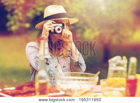 photography and people concept - close up of young woman with camera photographing at dinner in summer garden