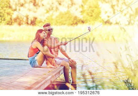 holidays, vacation, love and people concept - happy teenage couple taking picture by smartphone selfie stick and sitting on river berth at summer