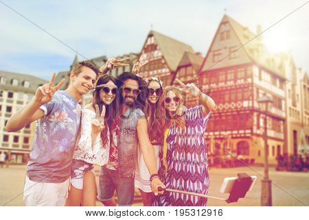 travel, tourism and people concept - smiling young hippie friends in sunglasses taking picture by smartphone selfie stick and showing peace sign over frankfurt am main city street background