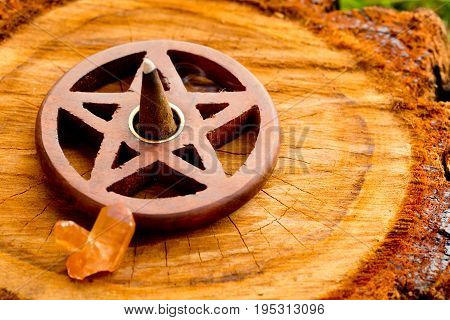 Burning Incense Cone  In Wooden Pentacle Incense Holder On Natural Cut Tree Log With Crystal