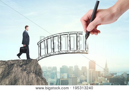Abstract image of businessman with briefcase crossing abstract bridge drawn by hand on city background. Help concept