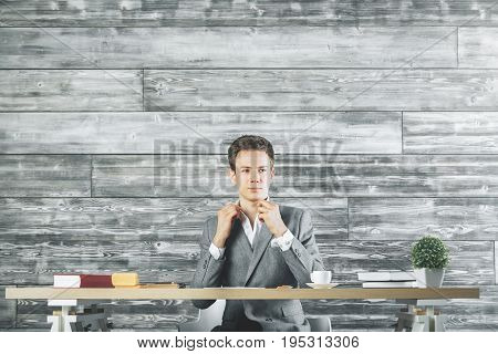 Portrait of handsome white man sitting at office table with coffee cup document supplies and other items. Wooden background