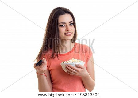 Cutie brunette smiling with tv remote and pop-corn isolated on white background