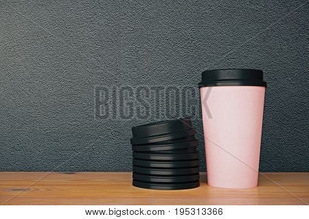 No logo pink take away coffee cup and pile of lids placed on wooden desktop. Grainy concrete wall background. Cafe advertising. Mock up 3D Rendering