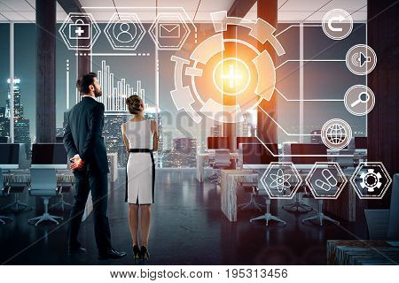 Back view of young businessman and woman looking at digital business hologram in night office. Technology future innovation and network concept. 3D Rendering