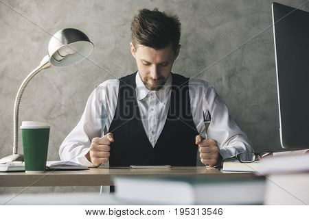 Crazy businessman about to eat cellphone with a knife and fork while sitting at wooden office desk with coffee cup and other items