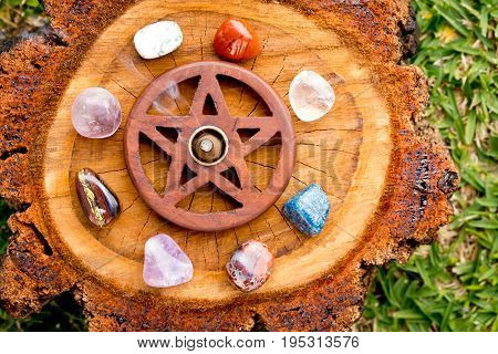 Burning Incense Cone  In Wooden Pentacle Incense Holder On Natural Cut Tree Log With Variety Of Crys