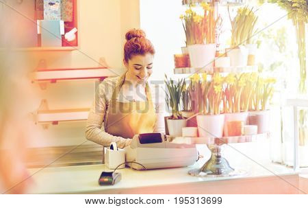 people, business, sale and floristry and concept - happy smiling florist woman at flower shop cashbox on counter