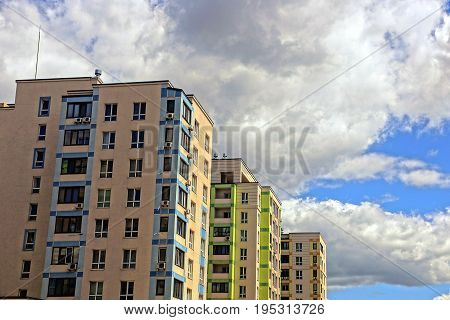 Modern multi-storey houses with windows and balconies against the sky and clouds