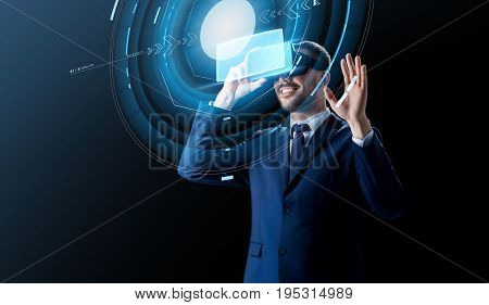 business, people and future technology concept - smiling businessman in virtual headset over black background with hologram