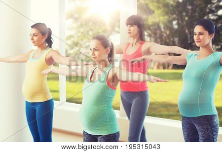 pregnancy, sport, fitness, people and healthy lifestyle concept - group of happy pregnant women exercising in gym over natural window view background