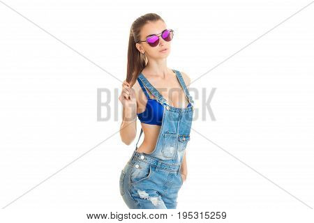 Sexual young girl with big silicon breasts in jeans overall and sunglasses isolated on white background