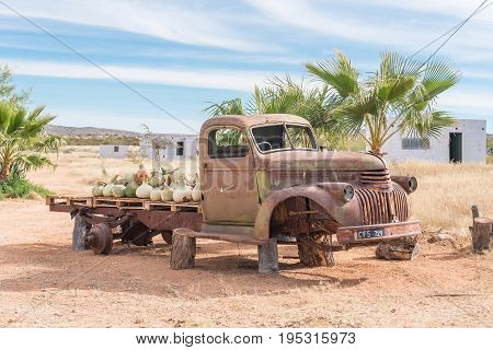 GROBLERSHOOP SOUTH AFRICA - JUNE 11 2017: The wreck of an old truck with a load of gourds at a farm stall on the N10 road between Groblershoop and Upington in the Northern Cape Province