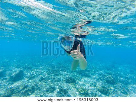Woman snorkeling in turquoise sea water. Snorkel shows thumb in full face mask. Beautiful girl swims in sea. Underwater photo of oceanic landscape. Seaside adventure. Summer water sport in tropic sea