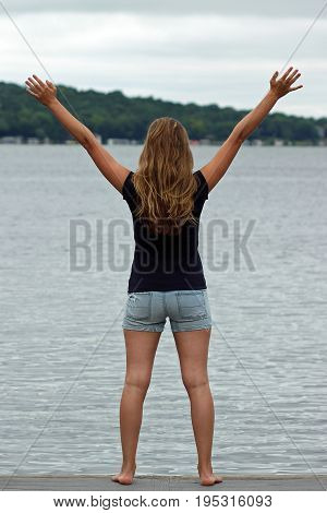 Young female standing on a pier in front of a lake wearing summer fashion with arms outstretched.