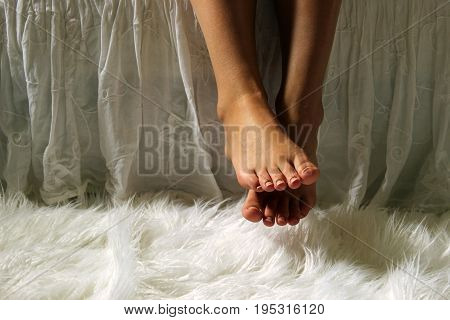 Female feet dangle over a bedside with white home décor accents. Copy space.