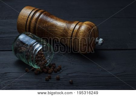 Jar With Black Pepper And A Mill On A Black Wooden Background