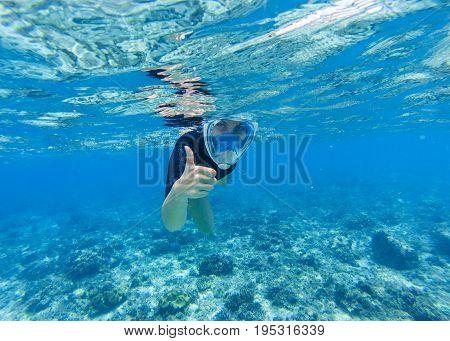 Woman snorkeling in shallow sea water. Snorkel shows thumb in full face mask. Beautiful girl swims in sea. Underwater photo of oceanic landscape. Seaside adventure. Summer water sport in tropic sea