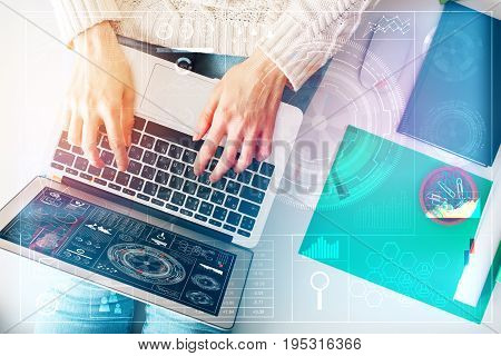 Top view of woman sitting on white office desktop with supplies and using laptop with abstract digital business hologram. Technology and finance concept. Double excposure