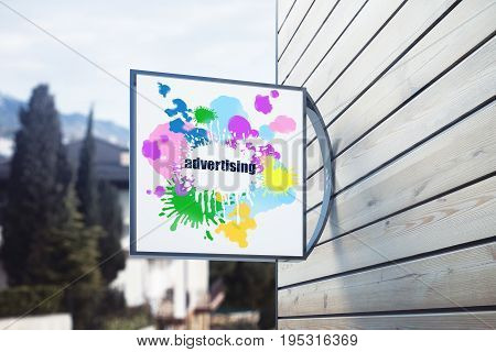 Square outdoor stopper with creative colorful sketch hanging on wooden plank building. Blurry trees in the background. Advertising concept. 3D Rendering