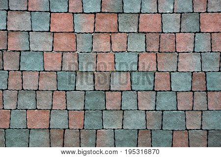 Texture of small colored square paving slabs on the road
