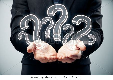 Businessman holding abstract drawn question marks on gray background. FAQ concept