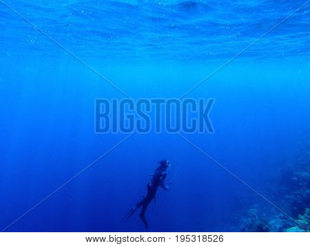 Diver underwater in deep blue sea. Man in diving gear dives up to water surface. Open water diving lesson. Beautiful ocean with sun rays in water. Diver man silhouette undersea photo. Seawater view