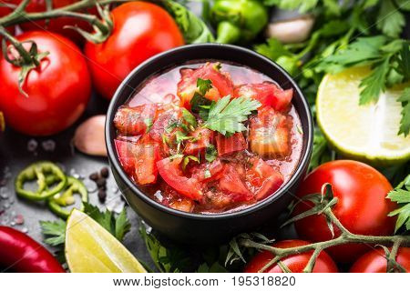 Traditional Latin American mexican salsa sauce and ingredients on black stone table.
