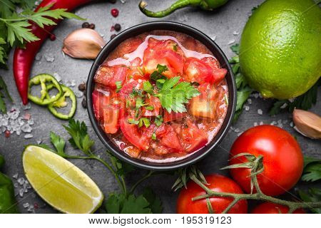 Traditional Latin American mexican salsa sauce and ingredients on black stone table. Top view.