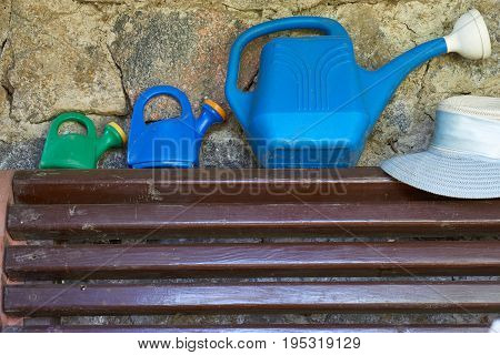 three different size of plastic watering cans for gardering and woman's summer hat on a brown wooden bench besides stone wall at the arbor in summertime. big one can for adult and other two for children like a toy