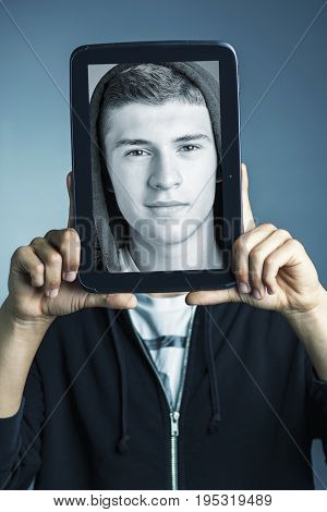 portrait of boy holding tablet with his face on it
