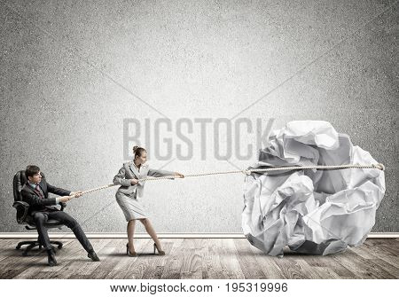 Young man and woman making huge paper ball move