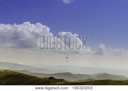 Summer view of Carpathian Mountains and Valleys, under blue sky with clouds. Mountain road goes on top of the hills on sunset landscape. With pair of paragliders in sky.
