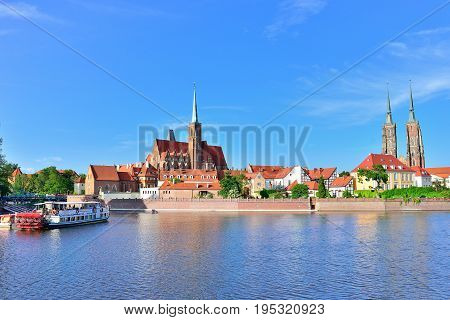 WROCLAW POLAND - JUNE 2017: View on Church of the Holy Cross and St. Bartholomew Odra river and Tumski Island Wroclaw Poland. A popular tourist place.