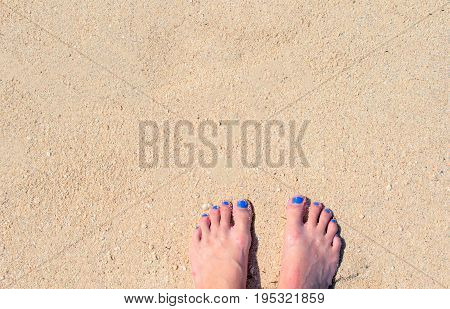 Woman feet on white sand. White coral beach by sea. Sunny tropical seaside. Summer vacation in paradise banner template. Woman feet on white sand beach.Perfect day on exotic island background image